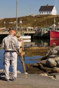 Artist painting boats in harbour